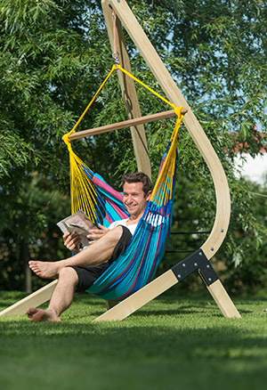 Mann liest im Hängestuhl ein Buch
