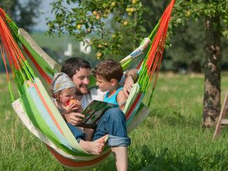 Hängesitz im Garten mit Papa und Kindern